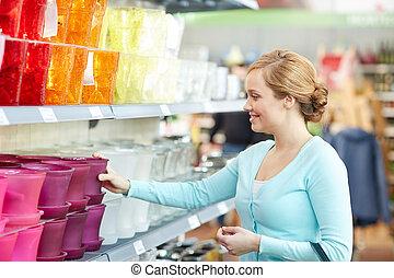 happy woman choosing flower pot in store
