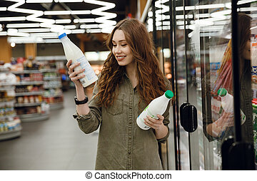 Happy woman choosing milk