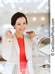 happy woman choosing pendant at jewelry store - sale,...