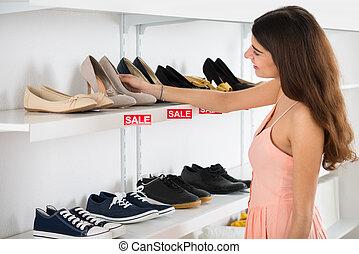 Happy Woman Choosing Shoes From Shelf In Store