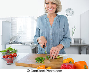 Happy woman chopping vegetables at the kitchen counter
