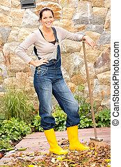 Happy woman cleaning backyard rake housework standing