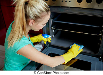 happy woman cleaning cooker at home kitchen - people,...