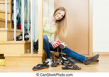 Happy woman cleaning footwear
