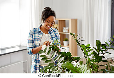 happy woman cleaning houseplant at home