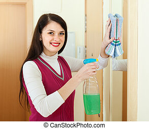Happy  woman cleaning  mirror  with detergent