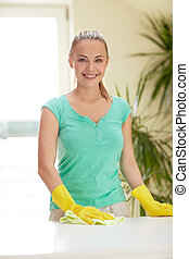 happy woman cleaning table at home kitchen - people,...