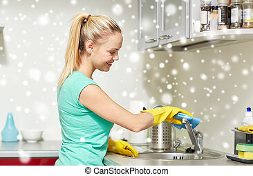 happy woman cleaning tap at home kitchen