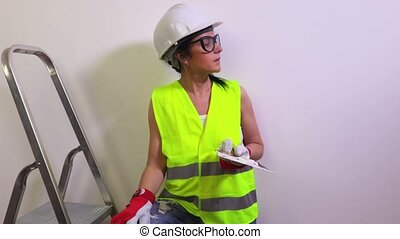 Happy woman construction worker near wall shows thumb up
