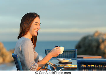 Happy woman contemplating in a coffee shop on the beach