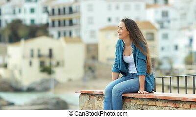 Happy woman contemplating ocean from a ledge in a coast town