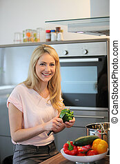 Happy woman cooking a meal in the kitchen