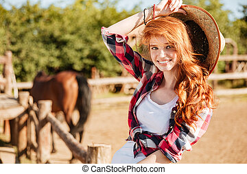 Happy woman cowgirl sitting and smiling on ranch - young...