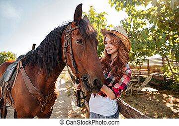 Happy woman cowgirl taking care of her horse on farm - Happy...