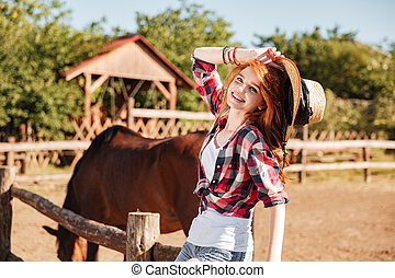 Happy woman cowgirl with horse on ranch - young woman...