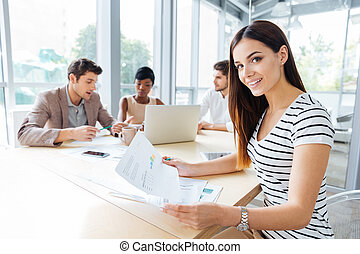 Happy woman creating presentation with her business team in office