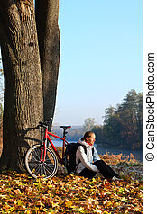 Happy woman cyclist enjoy the recreation autumn in nature -...