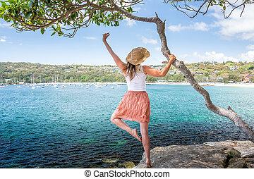 Happy woman dance pirouette beside tree by the ocean