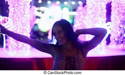 Happy woman dancing at Christmas lights bokeh at night on blurred background. 1920x1080
