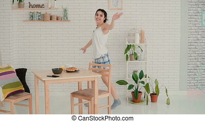 Happy woman dancing in kitchen wearing pajamas in morning. Brunette girl in cheerful mood haves fun alone. Slow motion.