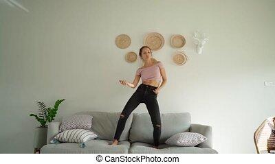 happy woman dancing jumping on sofa having fun enjoying playful dance. celebration successful achievement