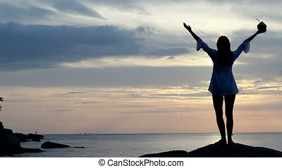 Happy woman dancing on the beach at sunset with sea background