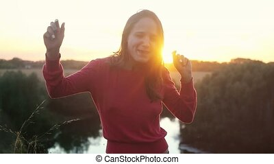 Happy woman dancing outdoors in slow motion during sunset.