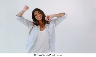 Happy woman dancing against a white background