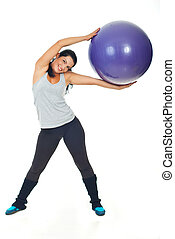 Happy woman doing exercise with pilates ball