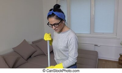 Happy woman doing housework and dancing