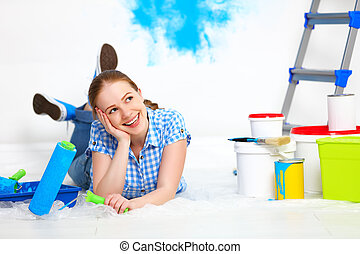 happy woman doing repairs, paint wall at home