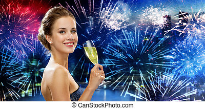happy woman drinking champagne over firework
