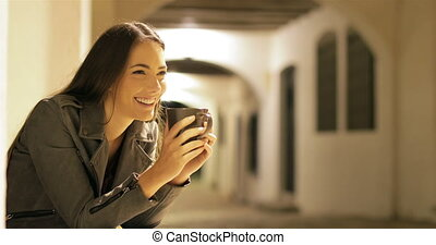 Happy woman drinking coffee in the night