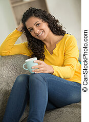 happy woman drinking coffee on a sofa at home