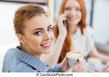 Happy woman drinking coffee with her friend in cafe