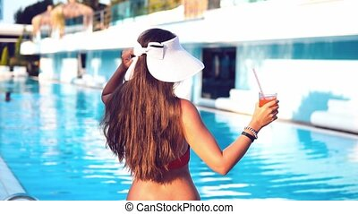 Happy woman drinking exotic cocktail in swimming pool