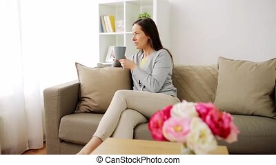 happy woman drinking tea or coffee at home - people,...