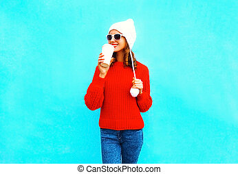 Happy woman drinks coffee in red sweater, hat on a blue background