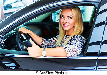 Happy woman driver showing thumbs up in her car