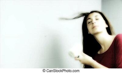 Cute young woman having fun drying long hair