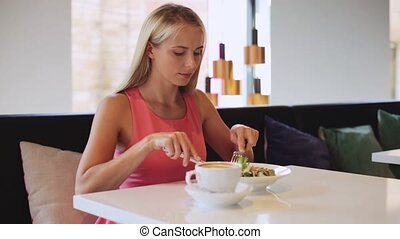 happy woman eating lunch at restaurant