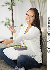 happy woman eating salad while watching tv