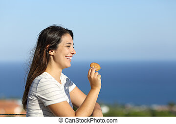 Happy woman eats cookie in a balcony on the beach