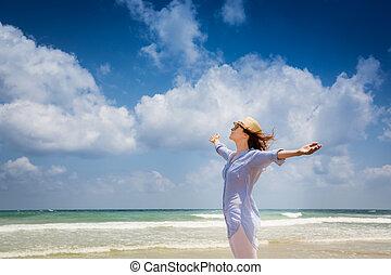 Happy woman enjoying at the beach