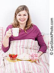 Happy woman enjoying breakfast in bed