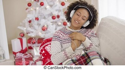 Happy woman enjoying her music at Christmas relaxing on a...