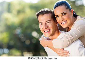 woman enjoying piggyback ride on boyfriends back - happy...