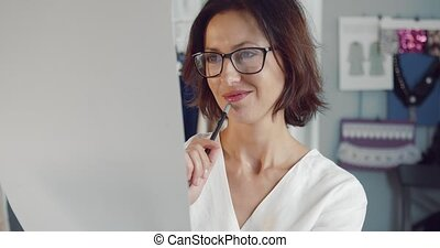 Portrait of happy woman in eyeglasses and white blouse looking at sketches while sitting in fashion studio. Smiling designer enjoying creative work and new clothing collection.