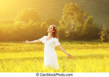 Happy woman enjoying summer meadow of yellow flowers