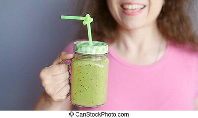 Happy woman enjoying vegetable smoothie